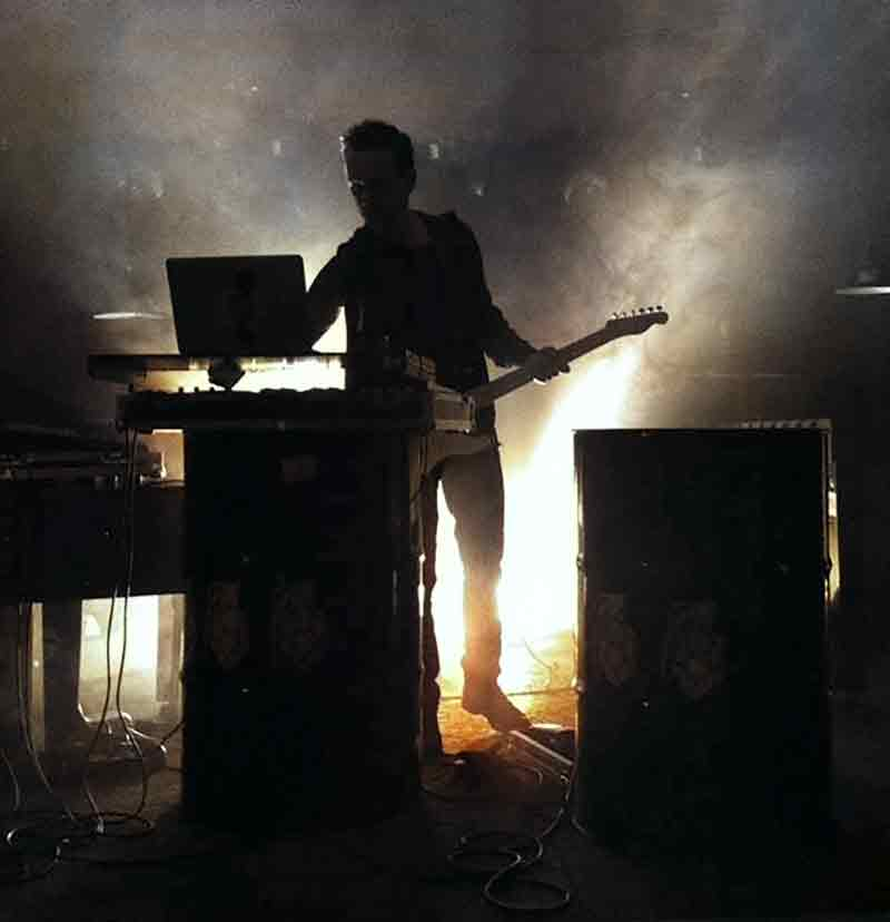 Musician with guitar and electronic instruments during live performance